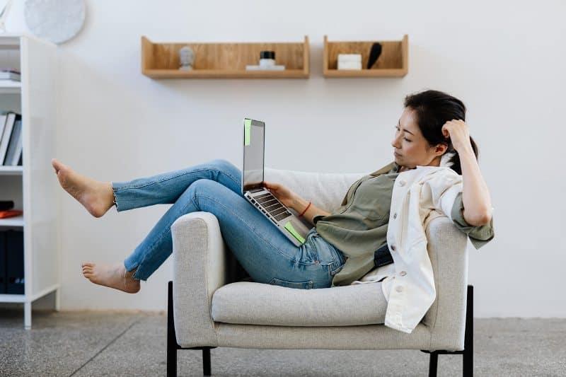 Дівчина на дивані з ноутбуком перекладає